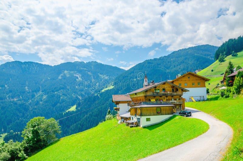 Высокогорное здание с зелеными лугами и высокими пиками стоковые изображения rf