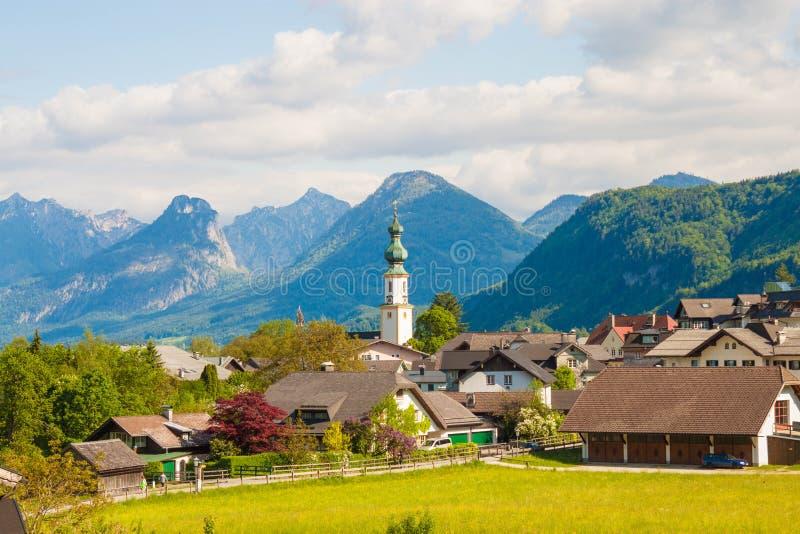 Высокогорный St Gilgen с церковью, горы деревни на предпосылке стоковое изображение