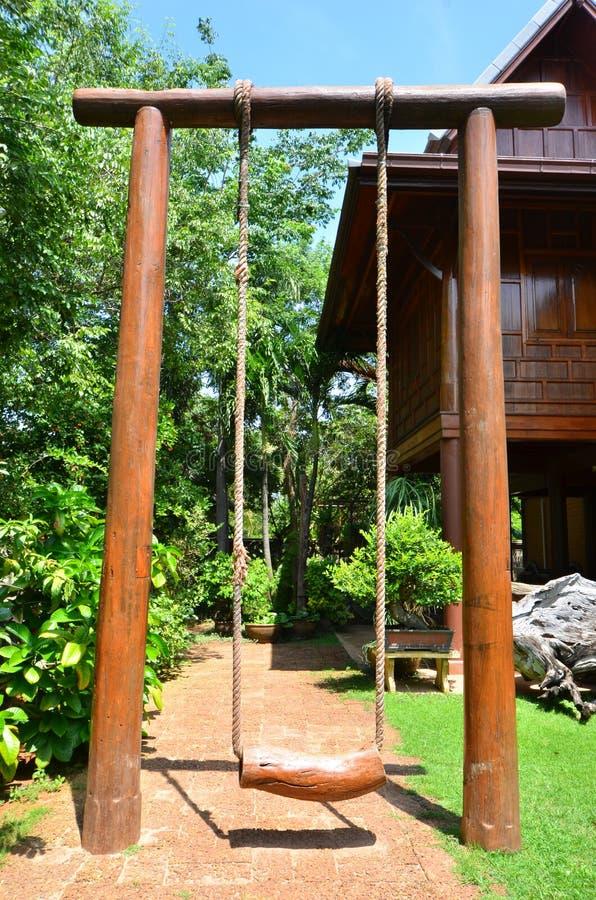Высокое деревянное качание с тайскими домом стиля и предпосылкой деревьев стоковое изображение rf