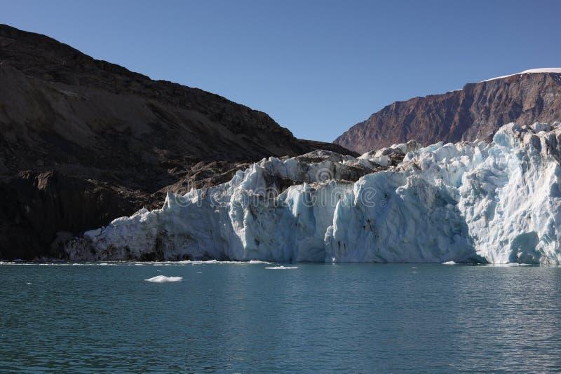 Высокое изображение разрешения конечной станции ледника и гористых стен фьорда в северо-восточной Гренландии стоковое изображение