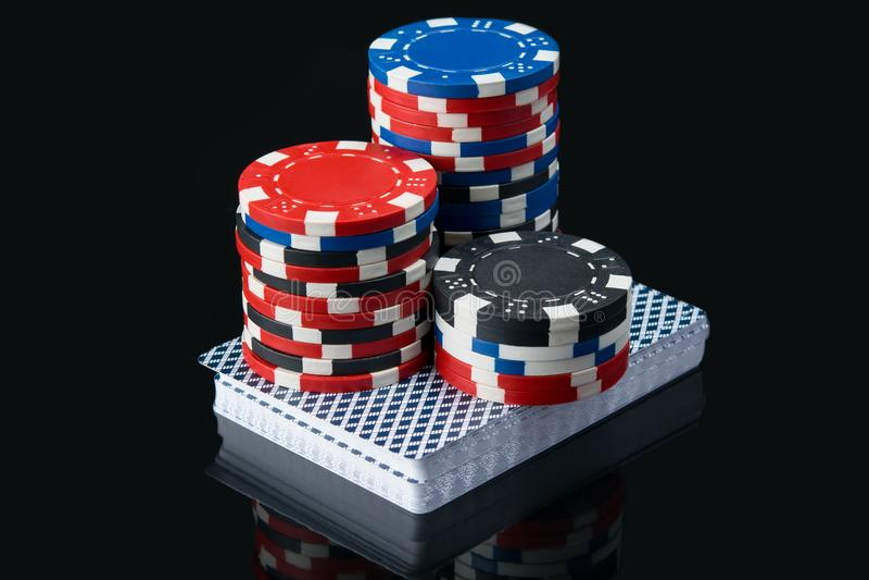 Высокое пари красных обломоков на палубе карточек игры, на черной таблице с отражением стоковая фотография rf