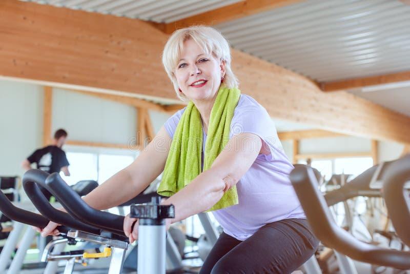 Высокопоставленная женщина тренируется для лучшей физической подготовки на велосипеде в тренажерном зале стоковая фотография rf