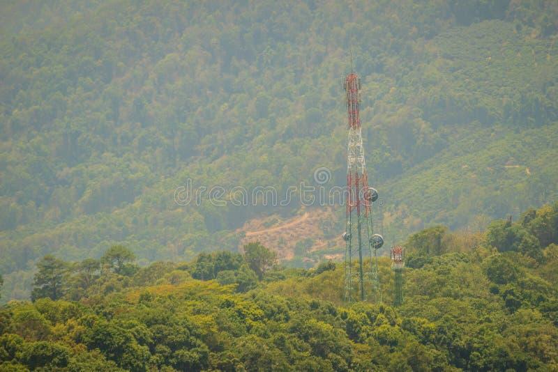 Высокорослая башня радиосвязи стоит внутри между зеленым цветом val стоковое фото rf