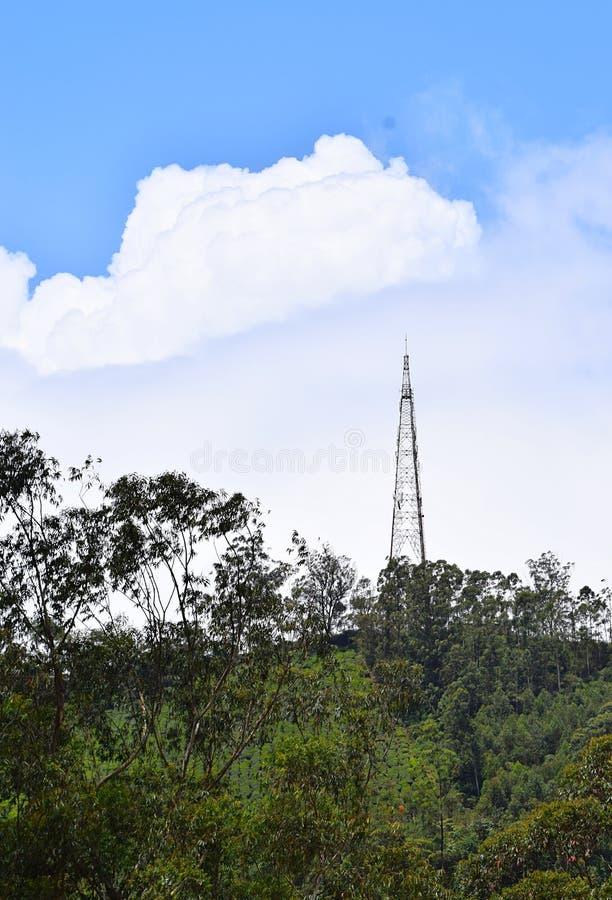 Высокорослая башня радиосвязи na górze холма с растительностью и белыми облаками в голубом небе стоковые фото