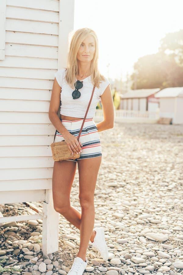 Высокорослая тонкая женщина в шортах в лучах солнца стоковые фото