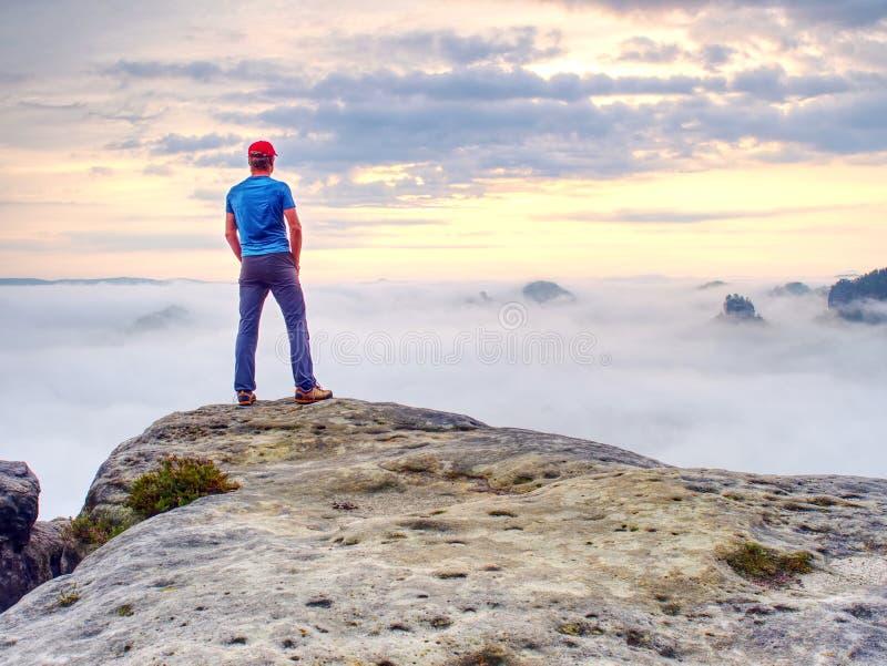 Высокорослый парень с руками в карманн в голубом положении рубашки и наблюдает горизонт стоковое изображение rf