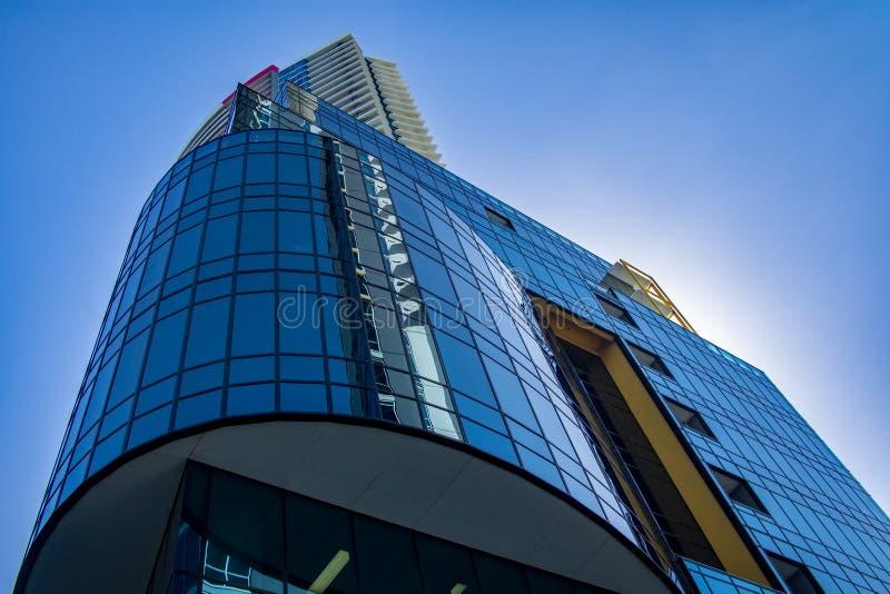Высокорослый стоящий жилой дом с темной отражая стеклянной стороной на более низких уровнях против голубого неба стоковое фото rf
