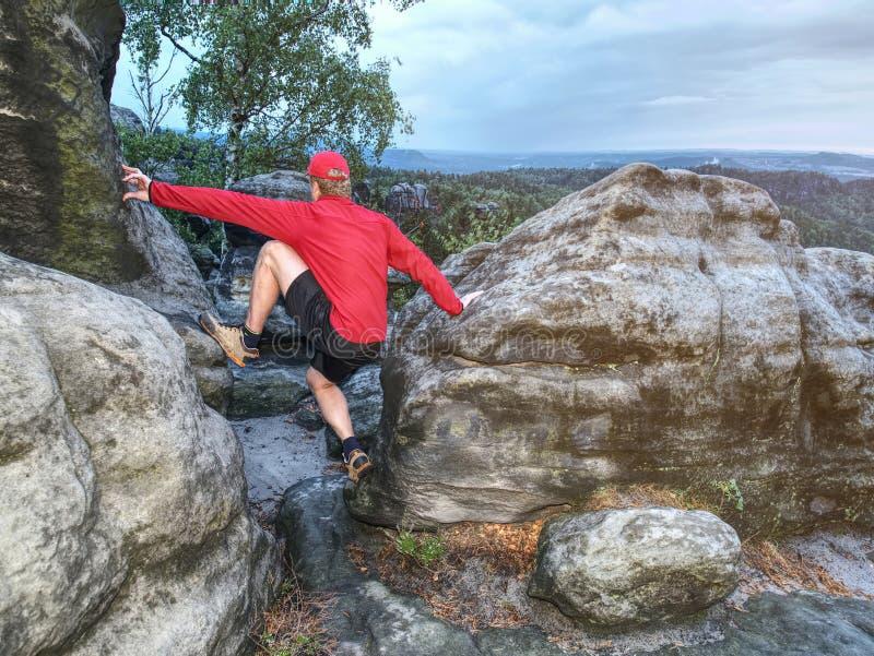 Высокорослый человек при крышка, красный шлямбур и брюки в пределах вечера падения стоковая фотография rf