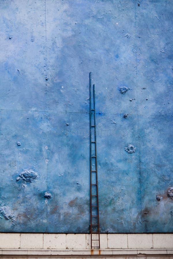 Высокорослая лестница на голубой стене стоковое изображение rf