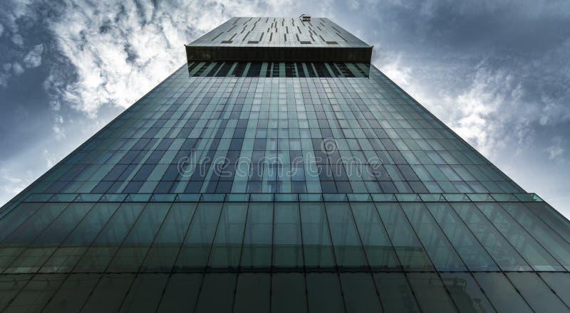 Высокорослый городской небоскреб в финансовом районе с унылыми драматическими облаками стоковая фотография rf