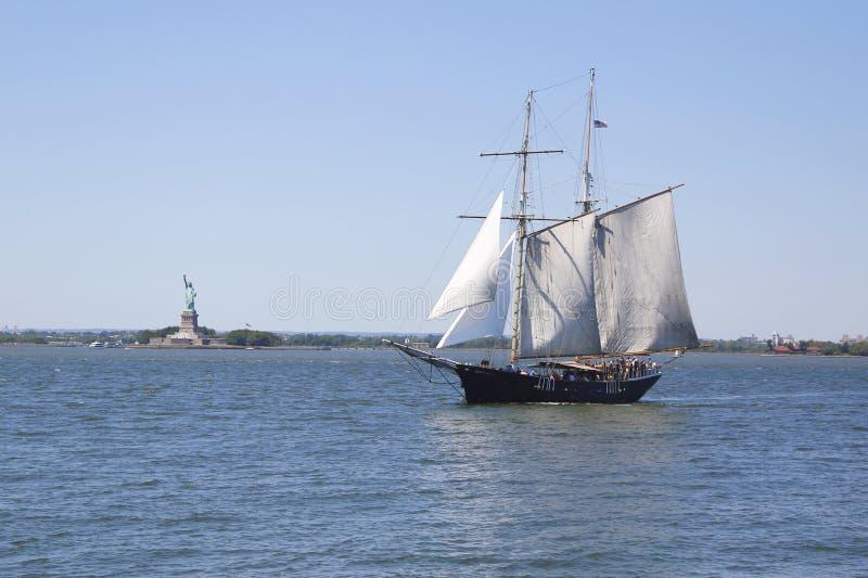 Высокорослый корабль рядом с статуей свободы стоковые фотографии rf