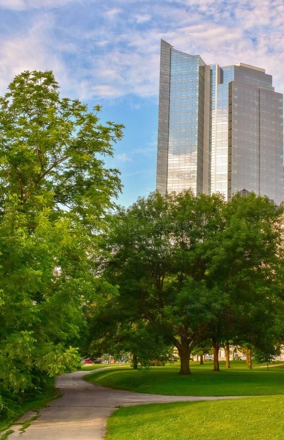 Высокоскоростной небоскрёб, стоящий над городским парком стоковые фотографии rf