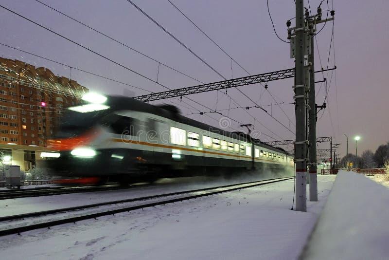 Высокоскоростной электропоезд пассажира вечером Луч фары поезда освещает падая снег стоковые изображения