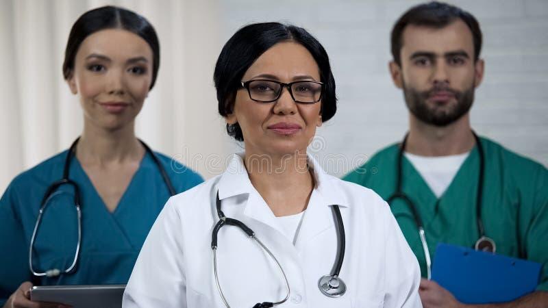 Высоко-квалифицированный хирург, медсестры готовые для того чтобы помочь пациентам, профессиональной медицинской бригаде стоковое изображение rf