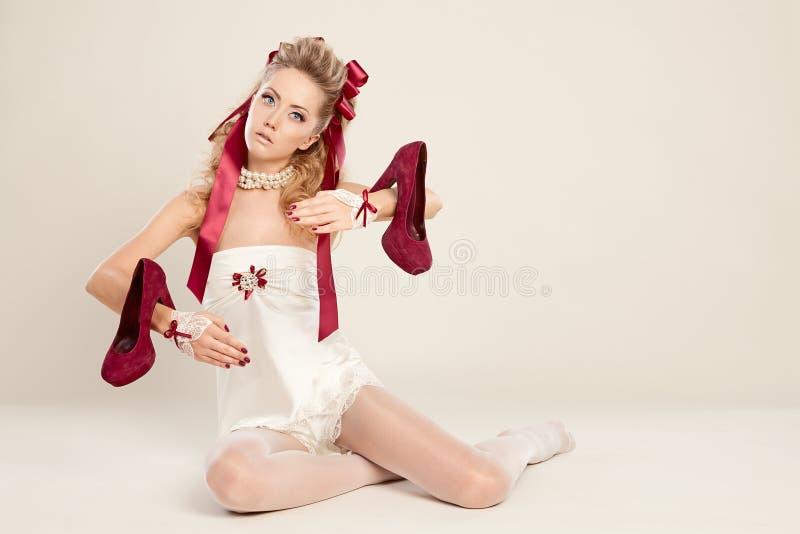 Высоко-накрененная молодая женщина в стиле куклы с красным смычком и красном цвете стоковые фотографии rf