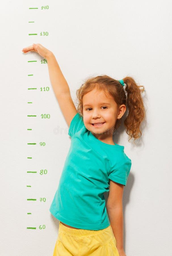 Выставка маленькой девочки как высокий она будет скоро стоковые фотографии rf