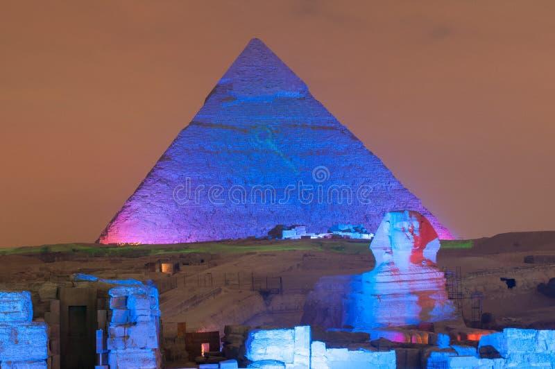 Выставка пирамиды Гизы и света сфинкса на ноче - Каире, Египте стоковое фото rf