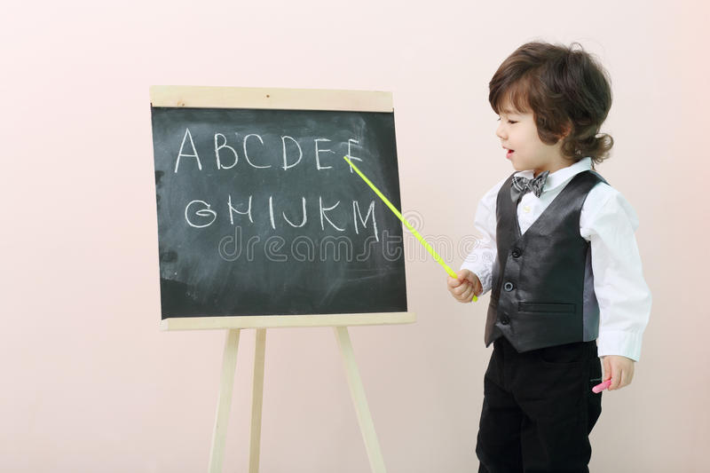 Выставки мальчика письмами указателя на доске стоковое изображение rf
