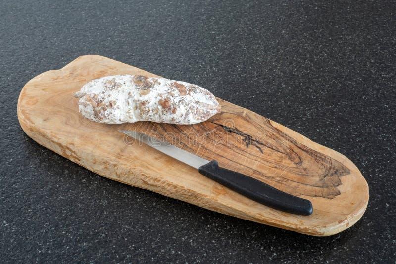 Высушенная сосиска и нож на древесине на черной таблице стоковое изображение rf