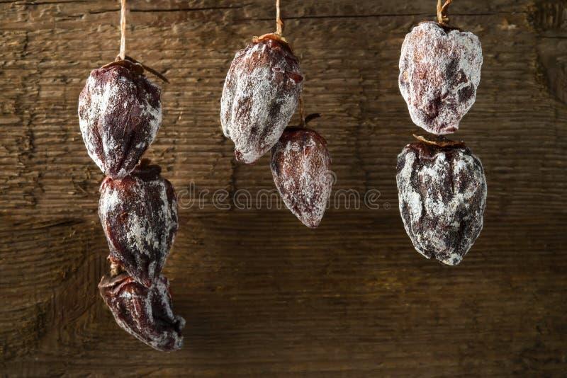 Высушенная хурма сушит на веревочке на фоне деревянной текстуры стоковая фотография rf
