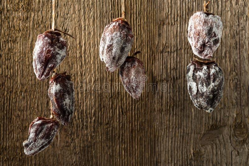 Высушенная хурма сушит на веревочке на фоне деревянной текстуры стоковая фотография