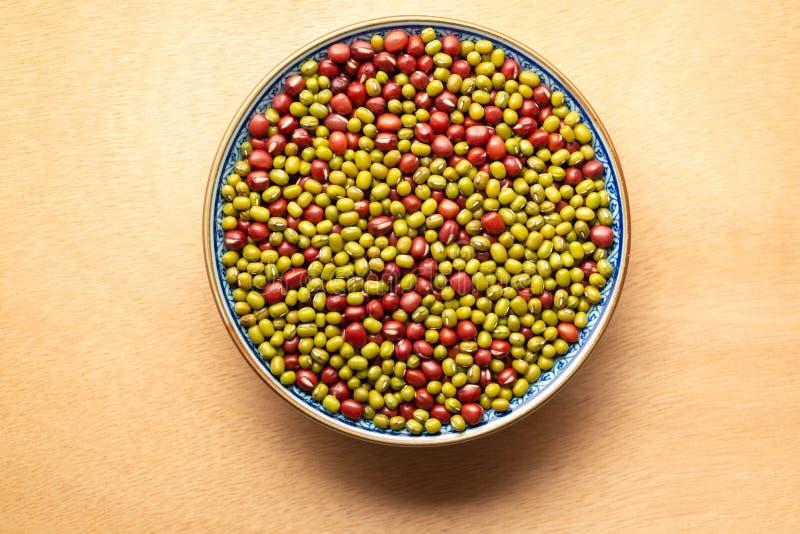 Высушенные красные и зеленые фасоли смешанные в одном шаре на деревянной предпосылке стоковое фото