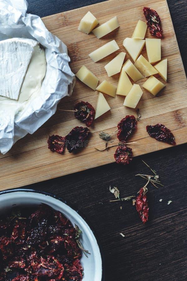 Высушенные красные томаты аранжировали с итальянским камамбером сыра на темной предпосылке Взгляд сверху Еда света предварительна стоковая фотография