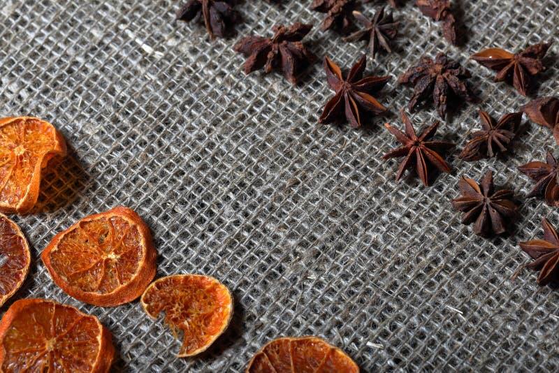 Высушенные куски апельсина и анисовки для украшения Положенный вне на грубую ткань белья стоковое изображение