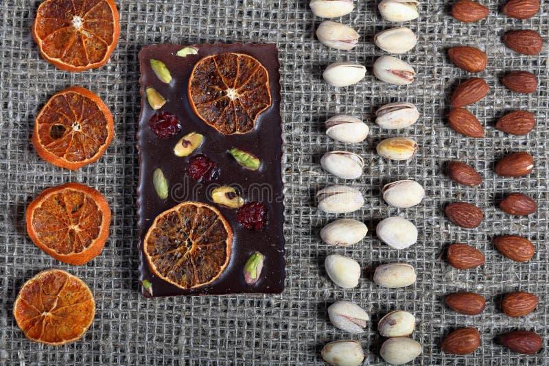 Высушенные оранжевые куски, фисташки и миндалины выровняны вверх в грубой ткани белья Темный шоколад украшенный с сухофруктом стоковые фото