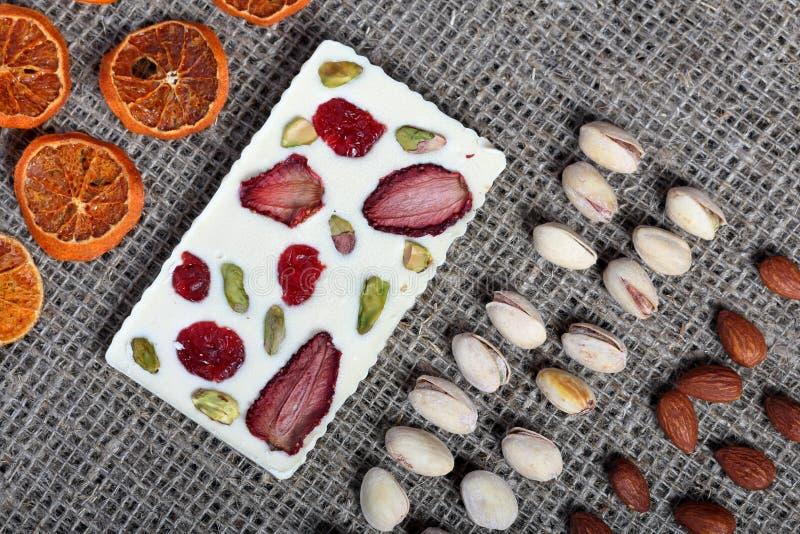 Высушенные оранжевые куски, фисташки и миндалины выровняны вверх в грубой ткани белья Белый шоколад украшенный с сухофруктом стоковые изображения rf