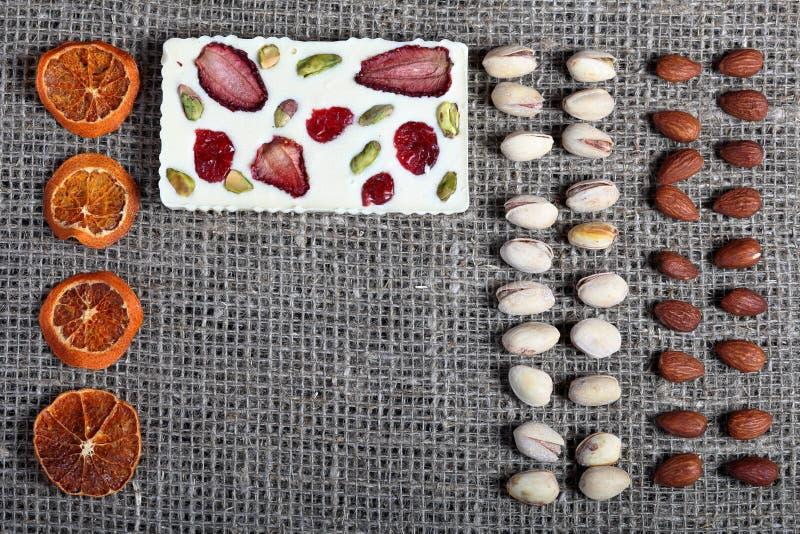 Высушенные оранжевые куски, фисташки и миндалины выровняны вверх в грубой ткани белья Белый шоколад украшенный с сухофруктом стоковые фото