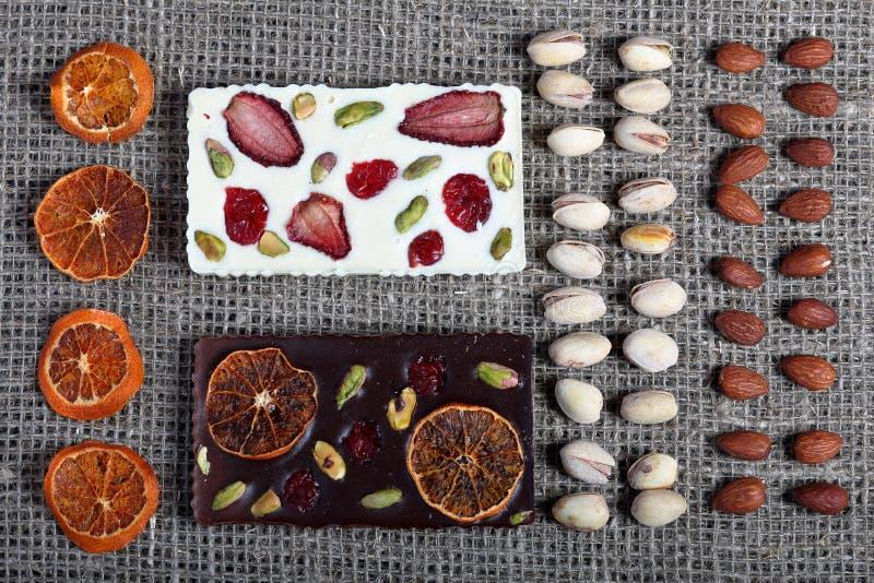 Высушенные оранжевые куски, фисташки и миндалины выровняны вверх в грубой ткани белья Темный и белый шоколад украшенный с высушен стоковое фото