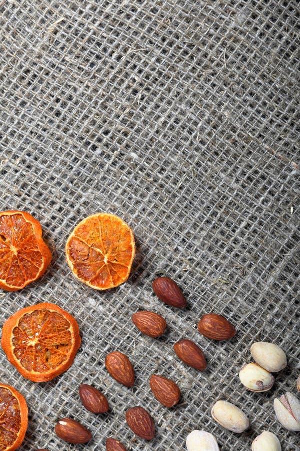 Высушенные оранжевые куски, фисташки и миндалины положены вне в строки на грубую ткань белья стоковые фотографии rf