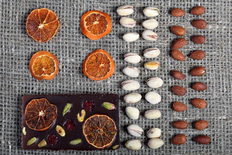 Высушенные оранжевые куски, фисташки и миндалины положены вне в строки на грубую ткань белья стоковая фотография