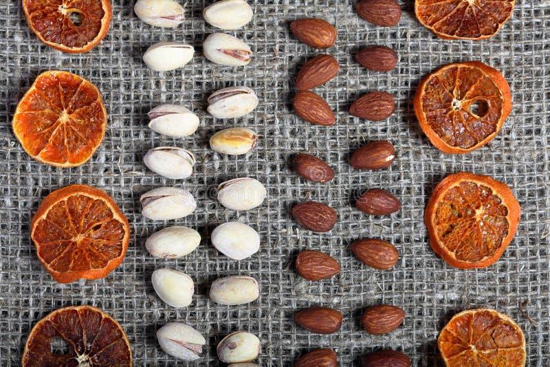 Высушенные оранжевые куски, фисташки и миндалины положены вне в строки на грубую ткань белья стоковые фото