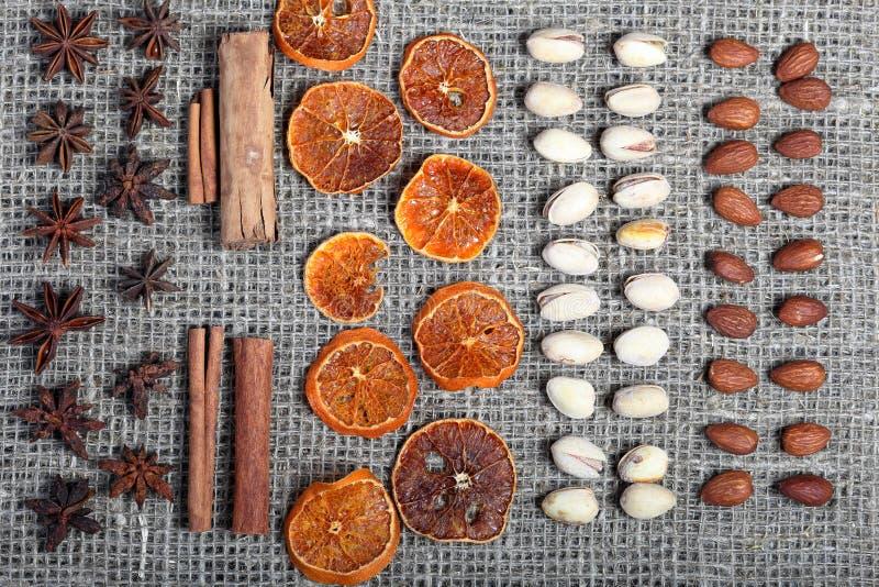Высушенные оранжевые куски, циннамон и анисовка для украшения Также фисташки и миндалины положены вне в строки на грубую ткань бе стоковое фото rf