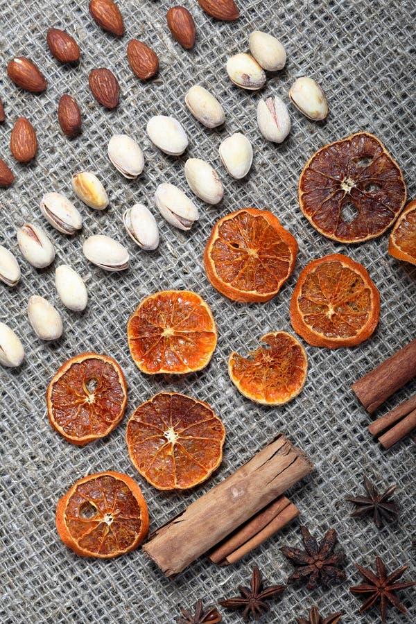 Высушенные оранжевые куски, циннамон и анисовка для украшения Также фисташки и миндалины положены вне в строки на грубую ткань бе стоковое изображение rf