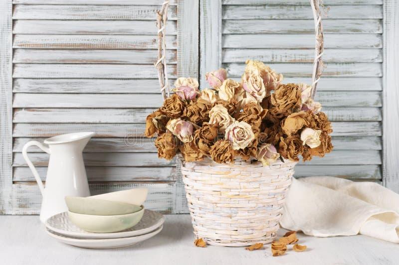 Высушенные розы в корзине против шторок стоковые изображения rf