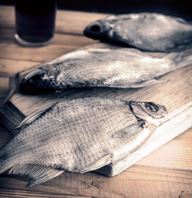 Высушенные рыбы на таблице и стекле пива стоковые фотографии rf