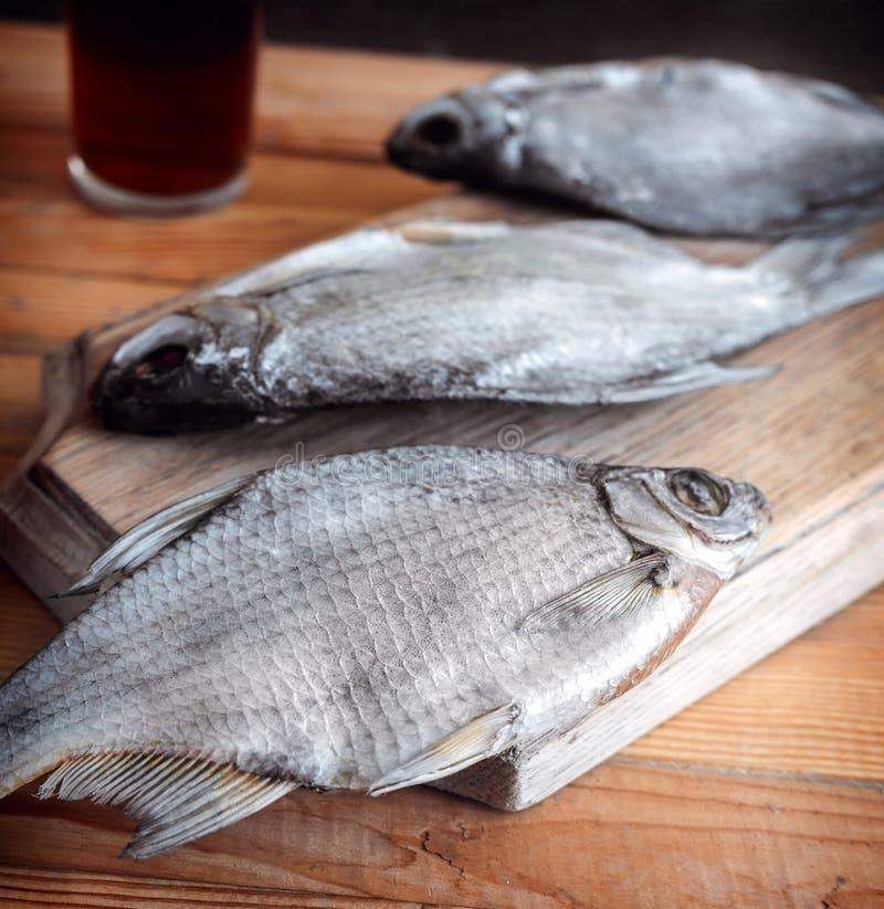 Высушенные рыбы на таблице и стекле пива стоковое фото