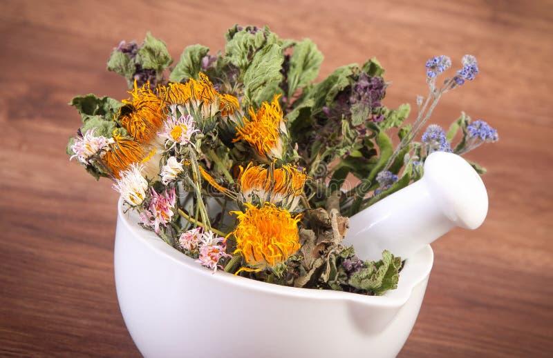 Высушенные травы и цветки в белом миномете, herbalism, украшении стоковая фотография rf