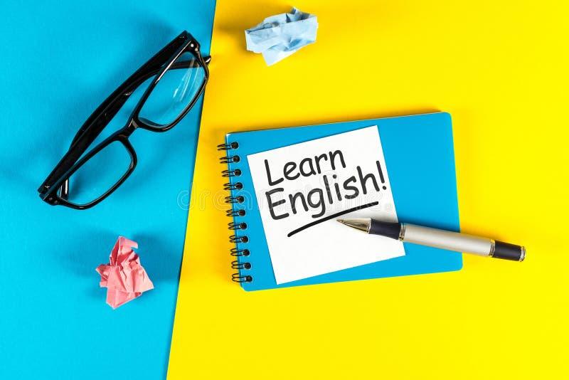 Выучите английский язык - примечание на голубой и желтой предпосылке с стеклами учителей стоковое фото rf