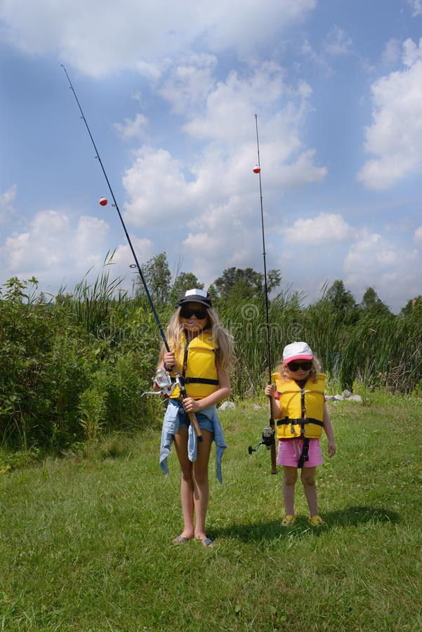 Выучите удить Изумительная белокурая маленькая девочка 2 с рыболовной удочкой готова удить Они носят в солнечных очках, спасатель стоковые фотографии rf