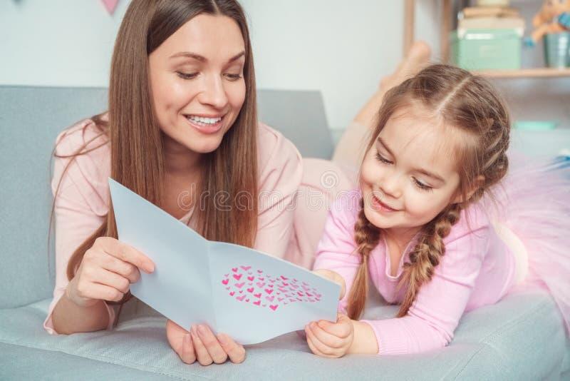 Выходные матери и дочери совместно дома на поздравлениях чтения софы стоковые изображения rf
