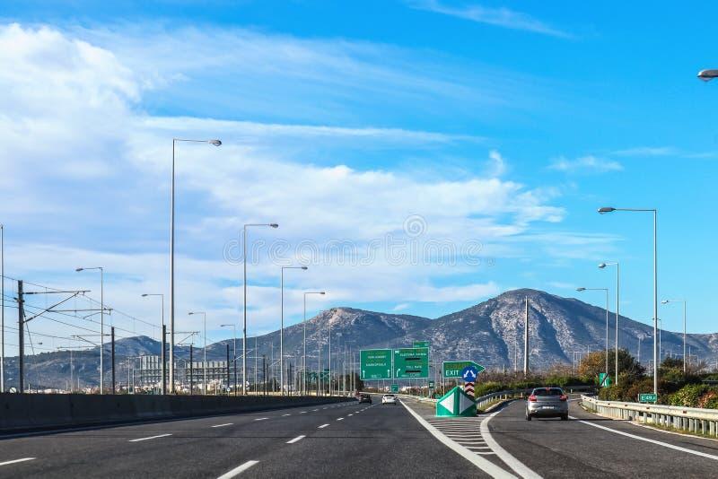 Выход на шоссе в Греции покидая Афина к полуострову Пелопоннеса с горами на заднем плане и знаками внутри греческими и стоковое изображение
