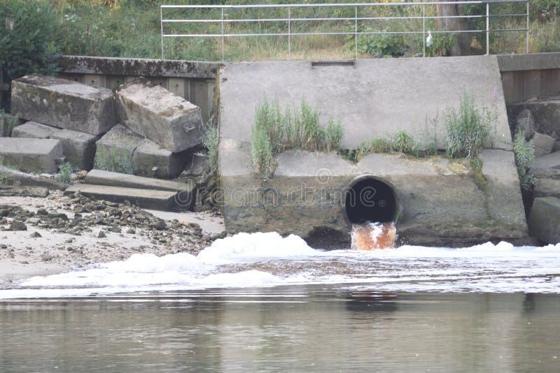 Выход сточных водов на реке с пеной и загрязнением стоковая фотография rf