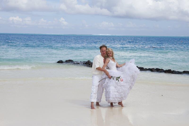 Выхольте и невеста на тропическом пляже стоковая фотография rf