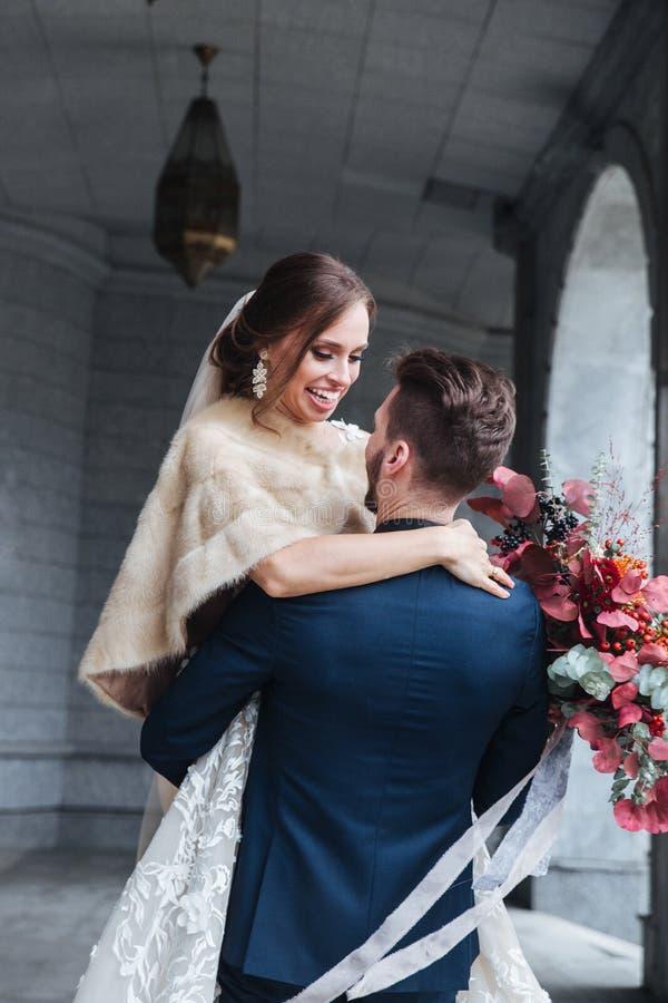 Выхольте поднятый невесте вверх в его оружиях Невеста в оружиях холит смеяться стоковая фотография