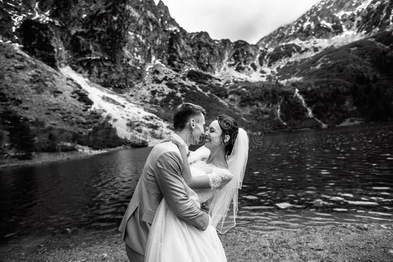 Выхольте целовать его молодую невесту, на береге озера Morskie Oko o Черно-белое фото стоковая фотография