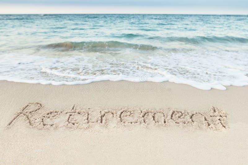 Выход на пенсию написанный на песке морским путем стоковое фото rf